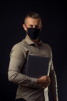 Hombre con laptop en máscara protectora. trabajo remoto