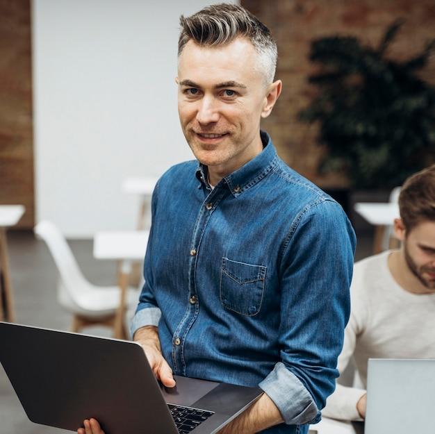 Hombre con laptop posando junto a compañero de trabajo