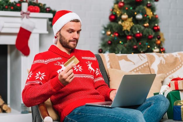 Hombre con laptop y tarjeta plástica