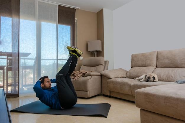 Hombre latino, haciendo ejercicio en su sala, hace abdominales, estiramientos y sentadillas