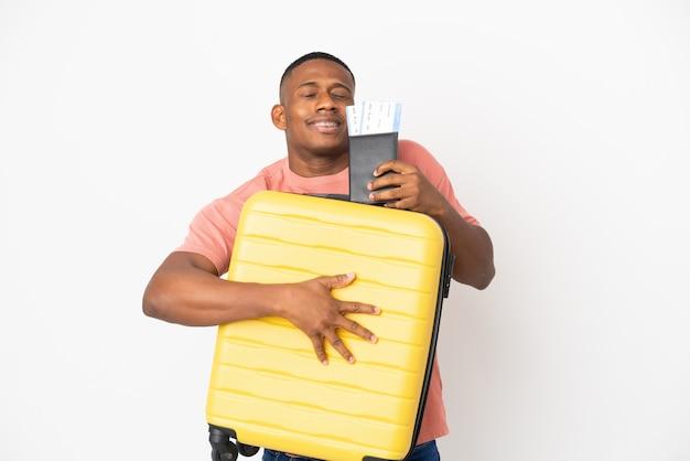 Hombre latino joven aislado en la pared blanca en vacaciones con maleta y pasaporte