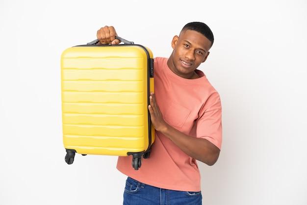 Hombre latino joven aislado en la pared blanca en vacaciones con maleta de viaje