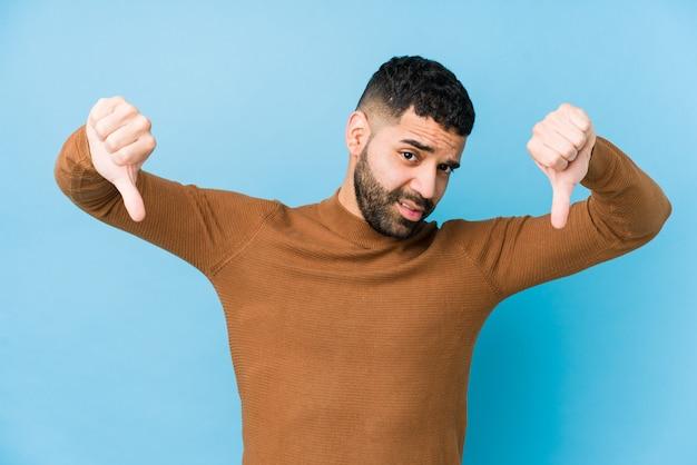 Hombre latino joven contra una pared azul aislada mostrando el pulgar hacia abajo y expresando aversión.
