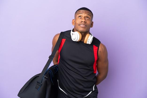 Hombre latino joven deporte con bolsa de deporte aislado