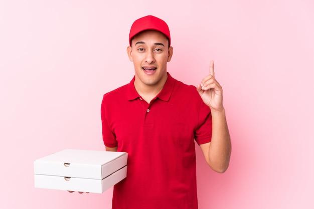 El hombre latino joven de la entrega de la pizza aisló tener una idea, concepto de la inspiración.