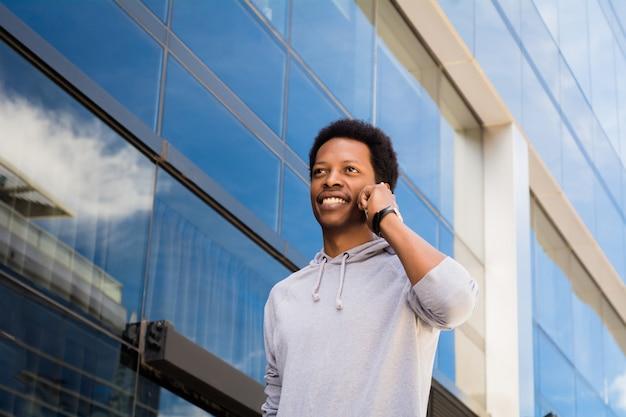 Hombre latino joven que habla en el teléfono móvil afuera.