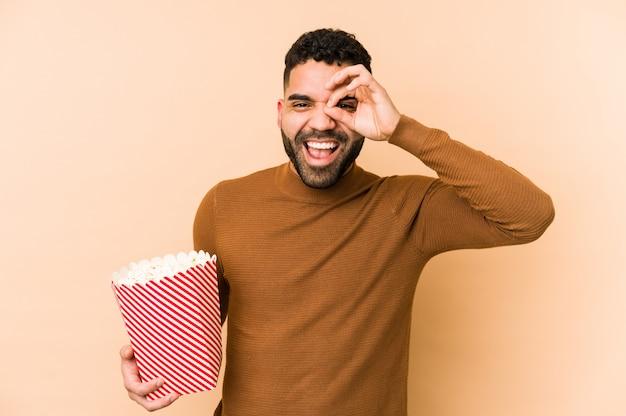 El hombre latino joven que sostenía una palomitas de maíz aisló excitado manteniendo gesto aceptable en ojo.