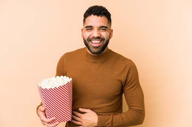 Hombre latino joven que sostiene una palomitas de maíz que ríe y que se divierte.