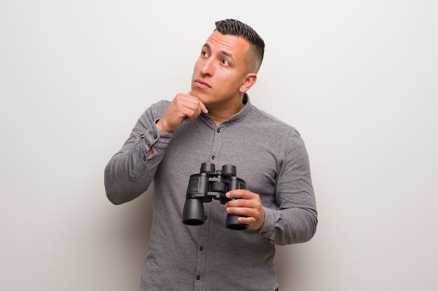 Hombre latino relajado pensando en algo mirando un espacio de copia. él está sosteniendo unos prismáticos.