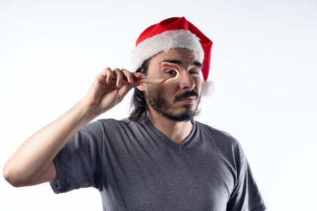 Hombre latino con sombrero de navidad jugando con un bastón de caramelo.