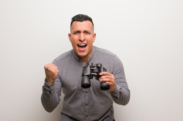 Hombre latino sorprendido y en shock. él está sosteniendo unos prismáticos.
