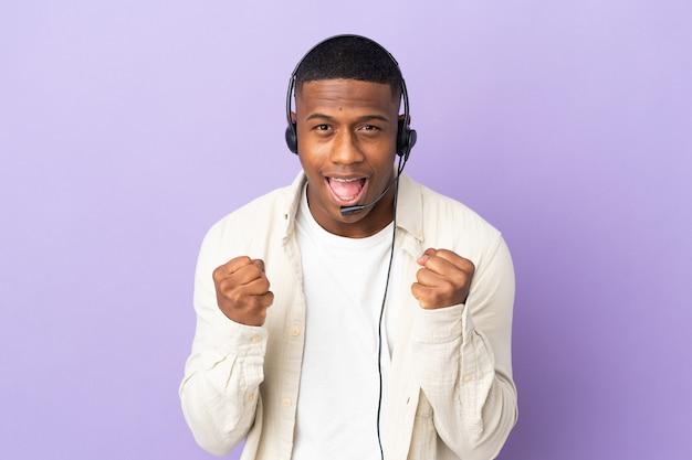 Hombre latino de telemarketing que trabaja con un auricular aislado en la pared púrpura celebrando una victoria en la posición ganadora