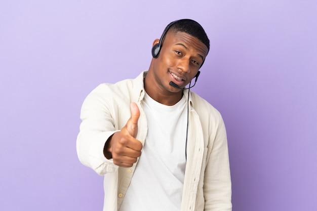 Hombre latino de telemercadeo que trabaja con un auricular aislado en la pared púrpura con los pulgares hacia arriba porque algo bueno ha sucedido
