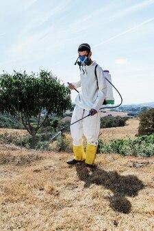 Hombre latino vistiendo ropa adecuada y máscara protectora rociando malezas en el terreno
