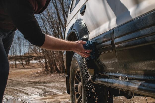 Un hombre lava el automóvil blanco y sucio al aire libre.