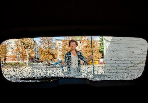 Hombre, lavado coche, vista trasera