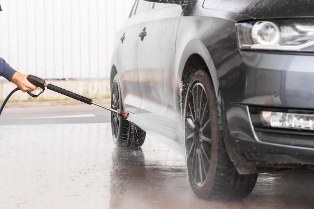 Un hombre está lavando un automóvil en el autoservicio de lavado de autos. la lavadora de vehículos a alta presión rocía espuma. mlada boleslav, 10.12.2019