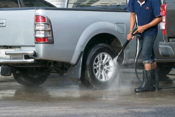 Hombre lavando el coche con agua a presión.
