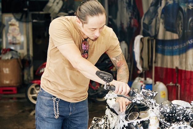 Hombre lavando la motocicleta con espuma limpiadora y agua después de un largo viaje
