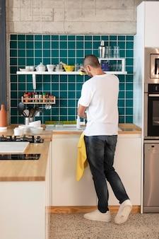 Hombre lavando platos de tiro completo