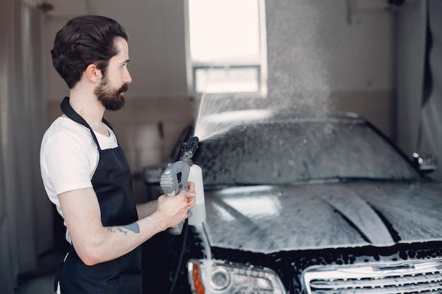 Hombre lavando su auto en un garaje