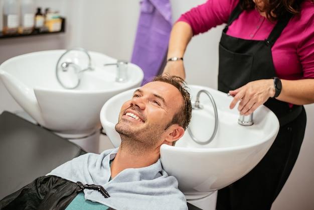 Hombre lavando su cabello en una barbería