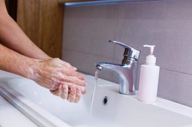 Hombre lavándose las manos con agua corriente, en un baño público.