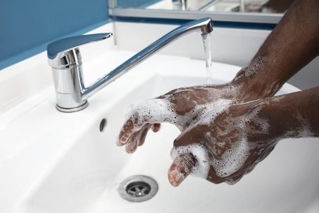 Hombre lavándose las manos cuidadosamente en el baño de cerca la prevención de infecciones