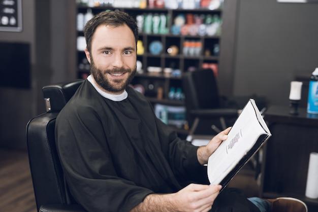 Un hombre lee un libro y se sienta en una barbería.