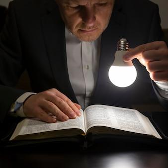 El hombre lee la santa biblia a la luz de la lámpara led encendida. la búsqueda de dios y el estudio del libro