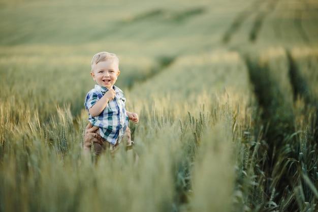 El hombre levanta al niño sobre su cabeza entre el campo