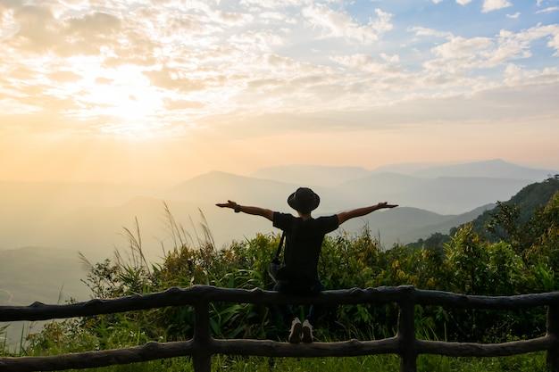 Un hombre se levanta para mirar la vista y el sol salir en el cielo de la mañana.