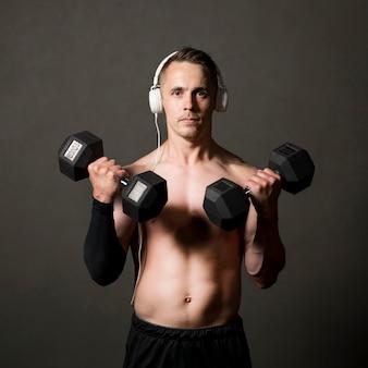 El hombre levanta pesas mientras escucha música