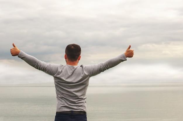 Hombre levantando los brazos junto a un lago