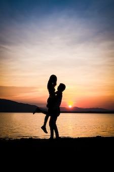 Un hombre levantando un fondo de mujer es lago montaña y puesta de sol