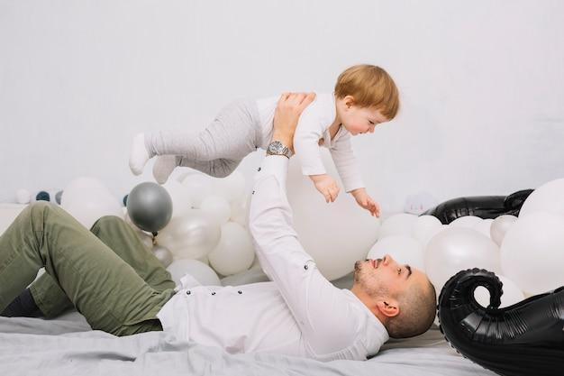 Hombre levantando pequeño bebé en las manos y acostado en la cama