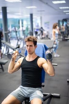 Hombre levantando pesas para ejercitar sus brazos y hombros en un gimnasio