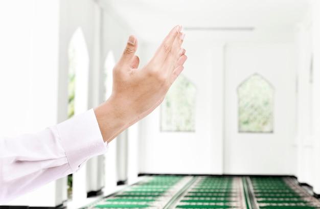 El hombre levantó las manos y rezó en la mezquita.