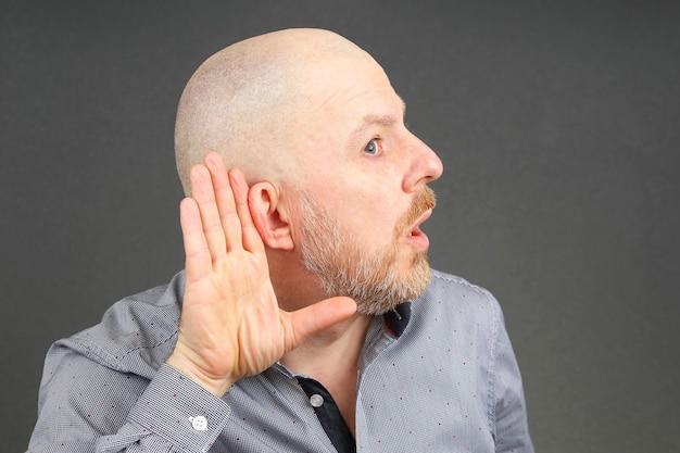 El hombre levantó los oídos a la audiencia con la mano.