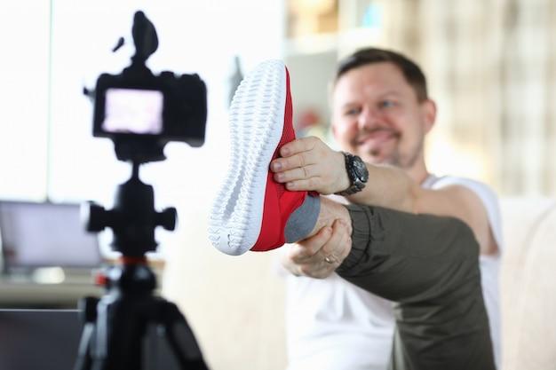 El hombre levantó la pierna y muestra zapatillas a la cámara