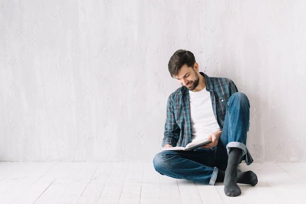 Hombre leyendo cerca de la pared