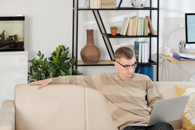 Hombre leyendo el documento en la computadora portátil