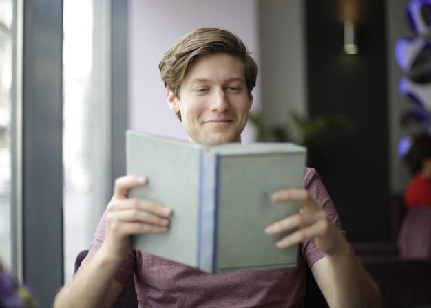 Hombre leyendo un libro en la cafetería.