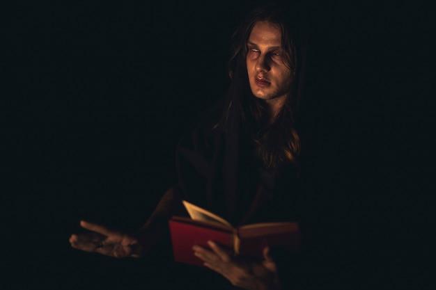 Hombre leyendo un libro de hechizos rojos en la oscuridad y mirando a otro lado