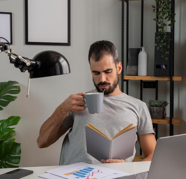 Hombre leyendo un libro y tomando café mientras trabaja desde casa