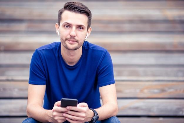 El hombre está leyendo un mensaje de texto en el teléfono móvil mientras camina en el parque