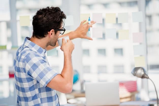 Hombre leyendo notas adhesivas mientras toma un café