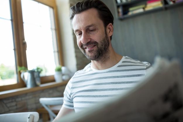 Hombre leyendo el periódico en la cafetería