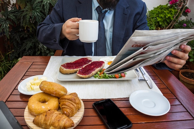 Hombre leyendo periódico mientras desayuna