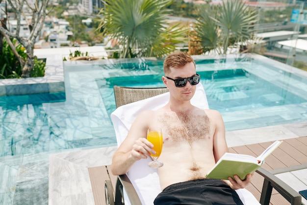 Hombre leyendo en la piscina